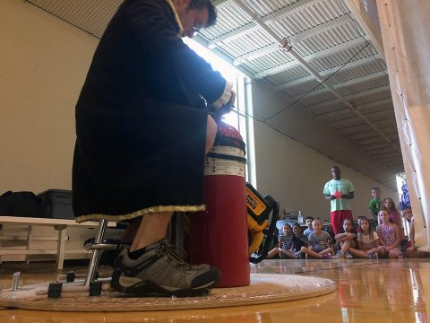 Austin Peay State University's Bryan Gaither prepares to don an Iron Man mask and his across the gym floor on his homemade hovercraft. Attendees of the university's Junior Govs Summer Camp are in the background. (APSU)