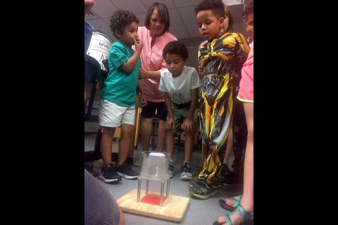 Kids watch as a metal ball moves SLOWLY through a liquid nitrogen-chilled magnet during a science demonstration at Austin Peay State University. (APSU)