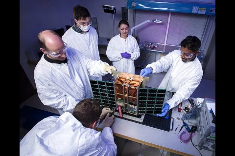 Technologists integrate a Goddard-developed instrument into Lawrence Livermore National Laboratory's (LLNL) CubeSat bus. Those pictured include LLNL's Lance Simms (front) and from left to right: Vincent Riot (LLNL), A.J. DiGregorio (Goddard), Jennifer Young (Goddard), and Guru Ramu (Goddard). (Lawrence Livermore Laboratory, LLNL-PHOTO-753023)