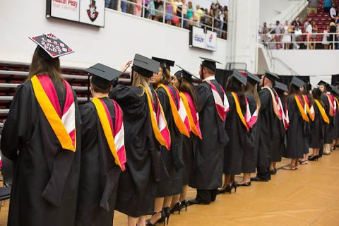 Austin Peay graduate students stand during commencement after receiving their graduate hoods. (Kim Balevre, APSU)