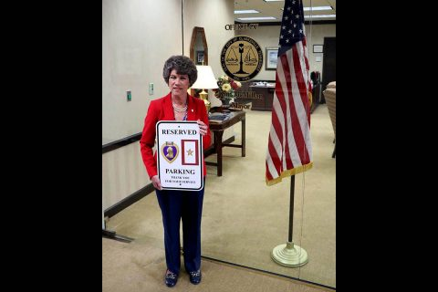 Clarksville Mayor Kim McMillan holds up one of the new reserved parking for Purple Heart recipients and Gold Star families signs.