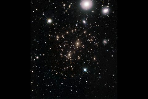 "This image shows a massive galaxy cluster embedded in the middle of a field of nearly 8,000 galaxies scattered across space and time. This ""galaxies galore"" snapshot is from a new Hubble Space Telescope survey to boldly expand its view by significantly enlarging the area covered around huge galaxy clusters previously photographed by Hubble. (NASA, ESA, A. Koekemoer (STScI), M. Jauzac (Durham University), C. Steinhardt (Niels Bohr Institute), and the BUFFALO team)"