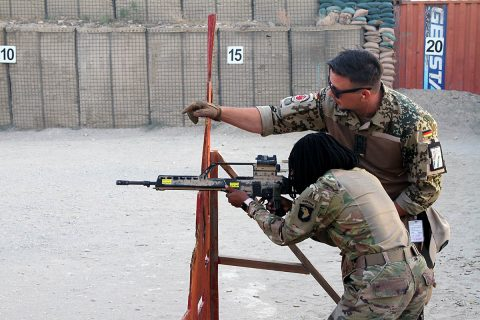 "German Sgt.1st Class Michael Michna, a combat medic and non-commissioned officer in charge of the ""Schutzenschnur"" event coaches Pfc. Winshelle Pierre, an automated logistics specialist with the 101st Resolute Support Sustainment Brigade while she fires the HKG36 rifle at Maholic Range, on Bagram Airfield, Afghanistan, September 14th, 2018. (Spc. Alexes Anderson, 101st Airborne Division (AA) Sustainment Brigade Public Affairs)"