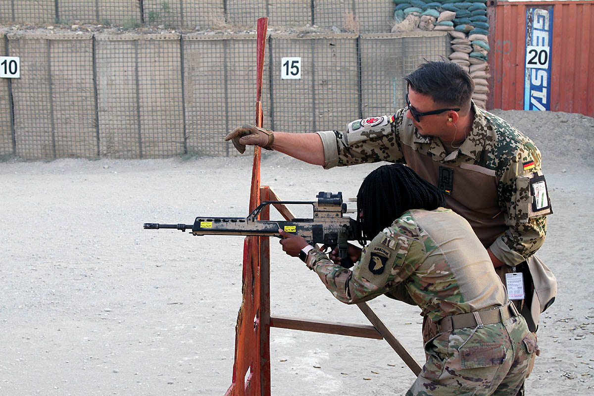 """German Sgt.1st Class Michael Michna, a combat medic and non-commissioned officer in charge of the """"Schutzenschnur"""" event coaches Pfc. Winshelle Pierre, an automated logistics specialist with the 101st Resolute Support Sustainment Brigade while she fires the HKG36 rifle at Maholic Range, on Bagram Airfield, Afghanistan, September 14th, 2018. (Spc. Alexes Anderson, 101st Airborne Division (AA) Sustainment Brigade Public Affairs)"""