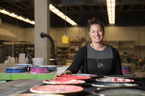 APSU grad student Melody Shipley stands with plates made as part of her art therapy project.