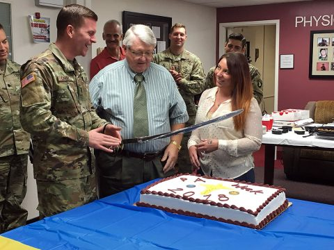 Fort Campbell's most senior physician assistant Terry Davis, (center) assigned to Blanchfield, newest physician assistant 1st Lt. Elizabeth McGrattan, assigned to the Tennessee National Guard, and the hospital's newest Interservice Physician Assistant Program Phase II student 1st Lt. Thomas Carroll cut a cake Oct. 11 at a luncheon and networking event at the hospital in honor of PA Week. (U.S. Army photo by Laura Boyd.)