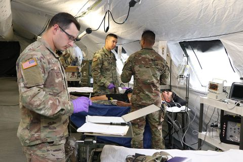 Sgt. Damien Colliver, Spc. Keith Gaston and Capt. Mark Cenon, all from the 41st Medical Detachment on Fort Campbell treat a simulated casualty in the new Intensive Care Unit of 586th Field Hospital during a training exercise on post. The two-week field exercise was the first for the 531st Hospital Center and seven of its direct reporting units since transitioning from the 86th Combat Support Hospital to the Army's new field hospital platform. (U.S. Army photo by Maria Yager)