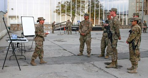 Sergeant Crystal Falcon (left), the support operations transportation contracting officer representative for the 101st Resolute Support Sustainment Brigade, speaks to her audience, instructing them on the proper way to determine the grid coordinates of a point on a military map, at Bagram Airfield, Afghanistan, Sept. 27, 2018. (SSG Caitlyn Byrne, 101st Sustainment Brigade PAO)