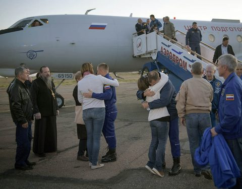 Expedition 57 Flight Engineer Alexey Ovchinin of Roscosmos, left, and Flight Engineer Nick Hague of NASA, right. embrace their families after landing at the Krayniy Airport, Thursday, Oct. 11, 2018. (NASA/Bill Ingalls)