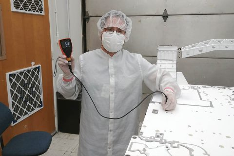 JPL mechanical technician Eduardo (Eddie) Castro uses a paint meter to measure the paint thickness on the Mars 2020 rover chassis. The reading on the meter indicates a thickness of 5.4 thousandths of an inch. The paint team wanted to achieve between four and six thousandths of an inch of paint after the application of three coats. (NASA/JPL-Caltech)