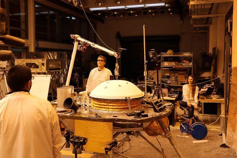 "NASA's InSight mission tests an engineering version of the spacecraft's robotic arm in a Mars-like environment at NASA's Jet Propulsion Laboratory. The five-fingered grapple on the end of the robotic arm is lifting up the Wind and Thermal Shield, a protective covering for InSight's seismometer. The test is being conducted under reddish ""Mars lighting"" to simulate activities on the Red Planet. (NASA/JPL-Caltech)"