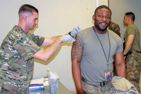 Specialist Phillip Pounders, a US Army combat medic assigned to the 101st Resolute Support Sustainment Brigade, inoculates Sgt. Michael Williams, an automated logistics specialist with the influenza vaccine at Bagram Airfield, Afghanistan, Oct. 17. (U.S. Army photo by Spc. Alexes Anderson)