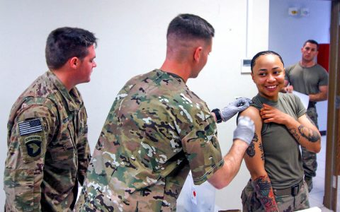 Specialist Phillip Pounders, a combat medic, assigned 101st Resolute Support Sustainment Brigade, inoculates Sgt. Brianna Sherpa, a construction equipment repair specialist, with the influenza vaccine at Bagram Airfield, Afghanistan, Oct. 17. (U.S. Army photo by Spc. Alexes Anderson)