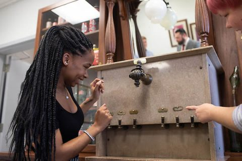 Austin Peay State University Graphic Design student Ebony Walton examines an old coke dispenser.