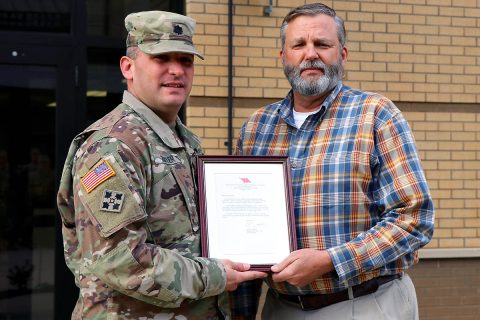 Fort Campbell Warrior Transition Battalion Commander, Lt. Col. Shawn Butler, recognizes John Holbrook for his selection as U.S. Army Medical Command's Warrior Care and Transition Program Transition Coordinator of the Year. (U.S. Army photo by Maria Yager)