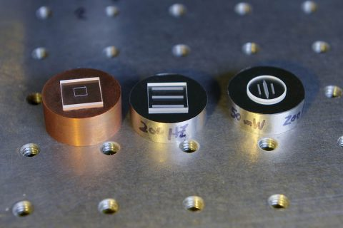 A Goddard team is using an ultrafast laser to bond dissimilar materials, with the goal of ultimately eliminating epoxies that outgas and contaminate sensitive spacecraft components. Shown here are a few samples (from left to right): silica welded to copper; silica welded to Invar; and sapphire welded to Invar. (NASA/W. Hrybyk)
