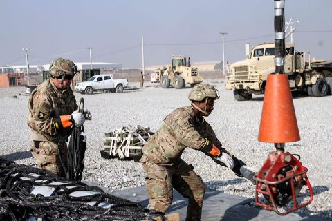 Staff Sergeant Timothy Adams (left), the 101st Special Troops Battalion master driver and sling load team member, works together with Sergeant Eric Greene (right), a native of Columbus, Georgia and a generator mechanic and sling load inspection certification course squad leader for the 101st Resolute Support Sustainment Brigade, on slinging a load of supplies for another forward operating base, on Bagram Airfield, Afghanistan, December 11th, 2018. (Sgt. Caitlyn Byrne, 101st Airborne Division (AA) Sustainment Brigade Public Affairs)