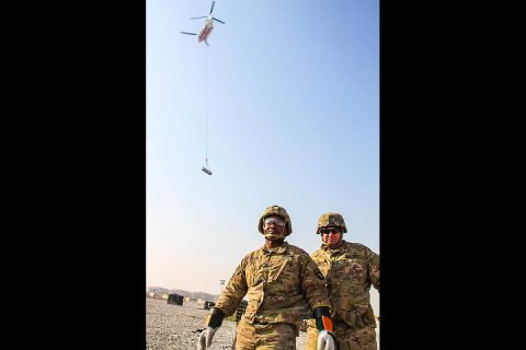 Staff Sergeant Timothy Adams (right), the 101st Special Troops Battalion master driver and sling load team member stands with Sergeant Eric Greene (left), a native of Columbus, Georgia and a generator mechanic and sling load inspection certification course squad leader for the 101st Resolute Support Sustainment Brigade, after completing a successful sling load mission, on Bagram Airfield, Afghanistan, December 11th, 2018. (Sgt. Caitlyn Byrne, 101st Airborne Division (AA) Sustainment Brigade Public Affairs)