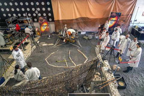 Engineers in Pasadena, California, sculpt a gravel-like material to mimic the terrain in front of NASA's InSight lander on Mars. Recreating the exact conditions will allow them to practice setting down the lander's instruments here on Earth before it's done on Mars. (NASA/JPL-Caltech/IPGP)