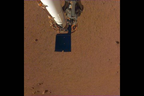 An image of InSight's robotic arm, with its scoop and stowed grapple, poised above the Martian soil. The image was received on Dec. 4, 2018 (Sol 8). (NASA/JPL-Caltech)