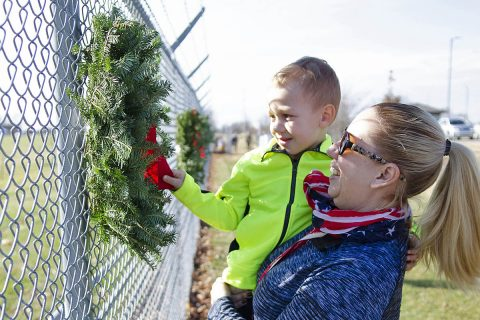 Kim Fields, Wreaths Across America volunteer, holds her 3-year-old grandson, Austin, Saturday, Dec. 15, 2018, as he straightens the velvet red bow on a wreath honoring fallen service members during a Wreaths Across America ceremony on Fort Campbell, Kentucky. More than 50 volunteers worked together to hang 101 wreaths along the fence inside T.C. Freeman Gate, Fort Campbell's main gate, to honor fallen service members. (Mari-Alice Jasper, Fort Campbell Courier)