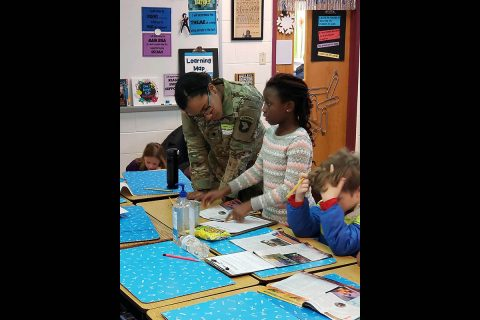 Spc. Morgan T. Henry, a medic assigned to Headquarters Company, 1st Battalion, 187th Infantry Regiment, 3rd Brigade Combat Team, 101st Airborne Division (Air Assault) looks at a student's art project during a visit to South Christian Elementary School Jan. 11. (1st Sgt. Jason Lyday)