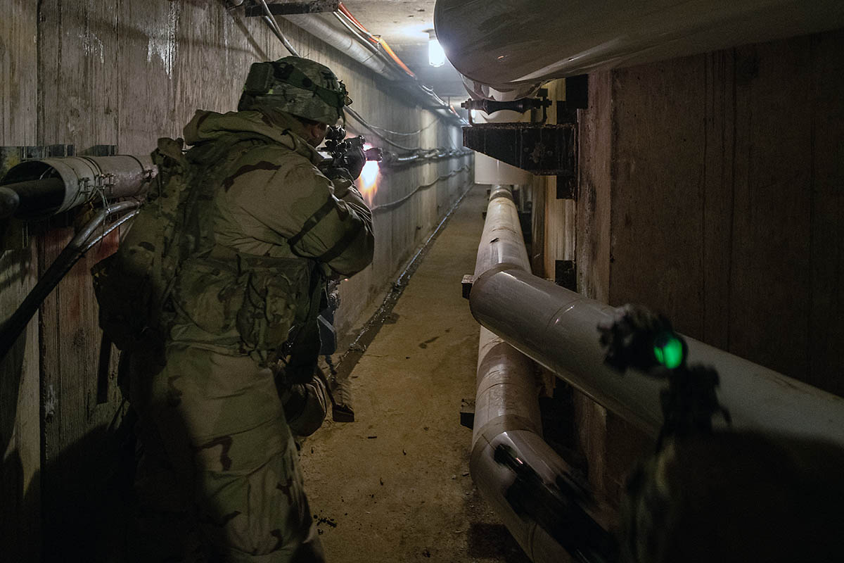 An infantryman with 1st Battalion, 187th Infantry Regiment, 3rd Brigade Combat Team, 101st Airborne Division (Air Assault) fires at notional opposing forces while clearing a tunnel system under the Muscatatuck Urban Training Center at Camp Atterbury, Indiana on Dec. 7, 2018. The tunnel system connected all the buildings. (Sgt. Patrick Kirby, 40th Public Affairs Detachment)