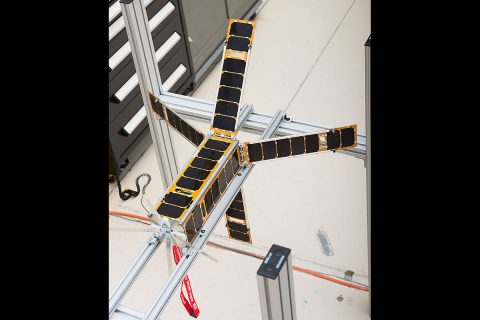 The ALBus CubeSat sits at NASA Glenn with its four solar array deployed. The solar arrays on this high-power CubeSat use a custom-designed shape memory alloy construction allowing for greater design flexibility. (NASA)