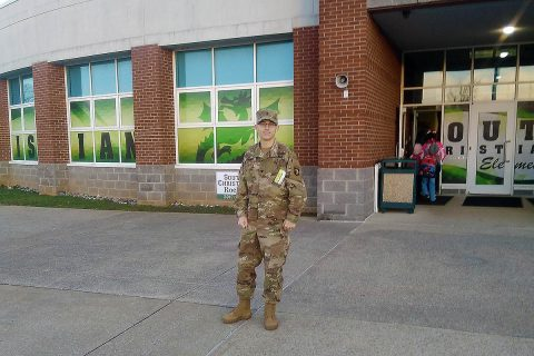 Spc. Grayson Sauer, an infantryman with C Co., 1st Battalion, 187th Infantry Regiment, 3rd Brigade Combat Team, poses in front of South Christian Elementary. (U.S. Army Photo by 1st Lt. John Radigan)