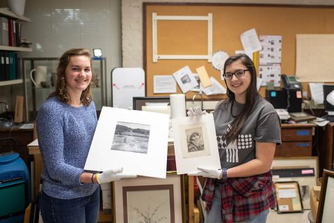 Austin Peay State University Art Students Sarah Potter and Katherine Tolleson hold their discoveries. Potter is holding a Philippe Halsman photo print of Winston Churchill, and Tolleson is holding a drypoint by Alphonse Legros.