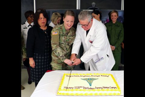 Blanchfield's most experienced nurse Jodie Hannes, a nursing supervisor, and youngest nurse 1st Lt. Nora Krueger, who recently reported to the hospital, cut a cake celebrating the 118th birthday of the Army Nurse Corps. A saber is used representing the Army Nurse Corps' commitment to military service so our nation may live in peace. (U.S. Army photo by Maria Yager)