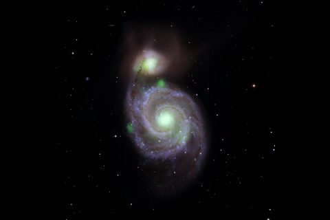 Bright green sources of high-energy X-ray light captured by NASA's NuSTAR mission are overlaid on an optical-light image of the Whirlpool galaxy (in the center of the image) and its companion galaxy, M51b (the bright greenish-white spot above the Whirlpool), taken by the Sloan Digital Sky Survey. (NASA/JPL-Caltech, IPAC)