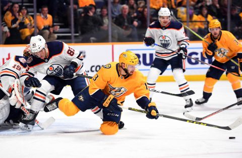 Nashville Predators center Nick Bonino (13) loses control of the puck after being checked by Edmonton Oilers defenseman Matt Benning (83) during the first period at Bridgestone Arena. (Christopher Hanewinckel-USA TODAY Sports)