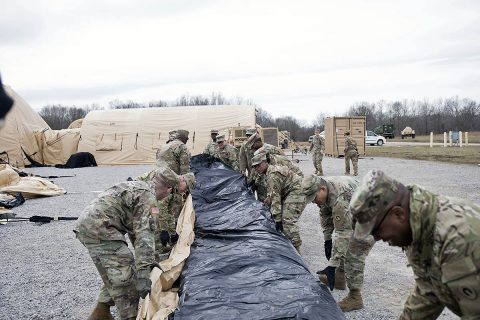 Soldiers from the Support Operations (SPO) section of the 1st Theater Sustainment Command unfold a large Airbeam tent Feb. 14, 2019 at Fort Campbell, KY. The tent is part of the unit's Early Entry Command Post. (Master Sgt. Jonathan Wiley)