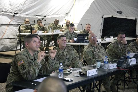 """Maj. Gen. Flem B. """"Donnie"""" Walker Jr., commanding general, 1st Theater Sustainment Command, along with his staff, listen to a brief Feb. 18, during the unit's Early Entry Command Post (EECP) exercise at Fort Campbell, KY. When Walker took command of the unit almost two years ago, he directed his staff to substantially increase the unit's expeditionary capabilities. (Master Sgt. Jonathan Wiley)"""