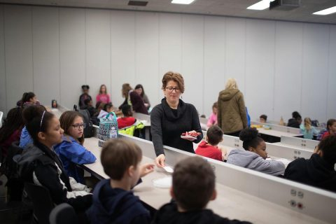 Austin Peay State University biology professor Dr. Mollie Cashner hands out supplies so the Moore Magnet Elementary fifth-graders can record their experiment results.