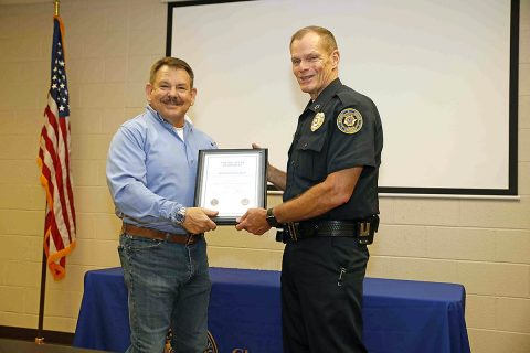Clarksville Police Chief Al Ansley congradulates Office Russ Baker on his 39 years of service to the department.