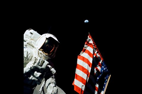 Geologist-Astronaut Harrison Schmitt, Apollo 17 Lunar Module pilot, is photographed next to the American Flag during NASA's final lunar landing mission in the Apollo series — a mission that included an instrument developed by Goddard scientist Otto Berg. The photo was taken at the Taurus-Littrow landing site. The highest part of the flag appears to point toward planet Earth in the distant background. (NASA)