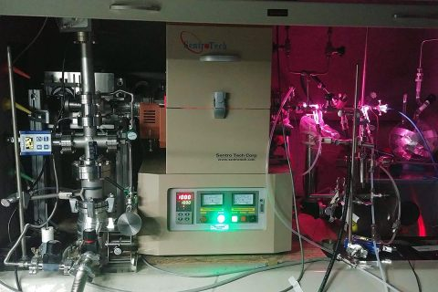 """JPL scientists used the """"oven"""" (center) to heat a mixture of hydrogen and carbon monoxide and subject it to UV radiation, generated by a hydrogen gas discharge lamp. The lamp radiates both visible light (the pink glow) and UV light, which enters the gas container inside the oven via a window on the right side. (NASA/JPL-Caltech)"""