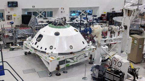With the backshell that will help protect the Mars 2020 rover during its descent into the Martian atmosphere visible in the foreground, a technician on the project monitors the progress of Systems Test 1. (NASA/JPL-Caltech)