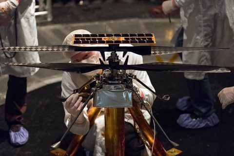 Members of the NASA Mars Helicopter team attach a thermal film to the exterior of the flight model of the Mars Helicopter. The image was taken on February 1st, 2019 inside the Space Simulator, a 25-foot-wide (7.62-meter-wide) vacuum chamber at NASA's Jet Propulsion Laboratory in Pasadena, California. (NASA/JPL-Caltech)
