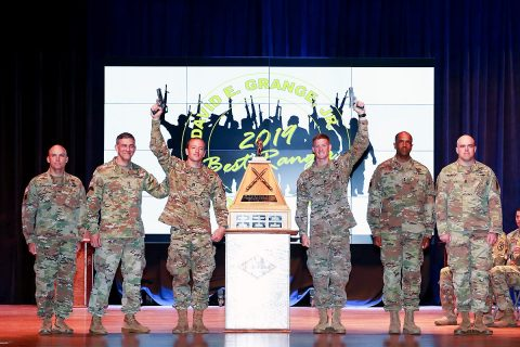 "Capts. Michael Rose, center left, and John Bergman, center, right, hold pistols above them after winning the 2019 Best Ranger Competition here April 15. Bergman and Rose of the 101st Airborne Division at Fort Campbell, Kentucky, earned the title of ""Best Rangers"" during an awards ceremony at the Maneuver Center of Excellence headquarters April 15 at Fort Benning. (U.S. Army photo by Markeith Horace, Fort Benning Public Affairs)"
