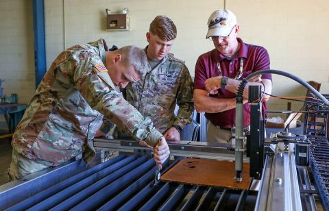 Soldiers of the 584th Maintenance Company, 129th Combat Sustainment Support Battalion, 101st Sustainment Brigade, 101st Airborne Division (Air Assault), measure the thickness of a piece of sheet metal, while civilian engineering instructors demonstrate how to use the plasma cutter machine.  (Staff Sgt. Caitlyn Byrne, 101st Sustainment Brigade Public Affairs)