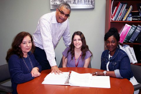 Keith Lampkin, director of the Clarksville Office of Housing & Community Development, discusses projects with staff members, from left, Jean Adcock, Brittney Cates and Lisa Walker.