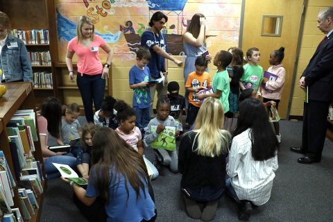 Several members of the Clarksville Mayor's Youth Council sit to read with Norman Smith Elementary School students following the donation of more than 700 books to the school. The council began a book drive last September and recently began distributing the collected books to a few elementary schools in the Clarksville-Montgomery County School System.