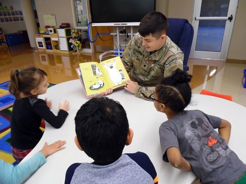 "Spc. Kyle Stouffer, a medic from the 551st Military Police Company, 716th Military Police Battalion, captivates students at Marshall Elementary School (MES) for ""Read Across America."" MES is an official partner school for the 716th MP BN on the installation. (101st Airborne Division (AA) Sustainment Brigade Public Affairs)"