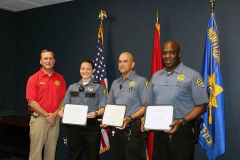 Montgomery County Sheriff's John Fuson congratulates Camilla Kent, Daniel Kowal, and Douglas Thomasson on their promotions.