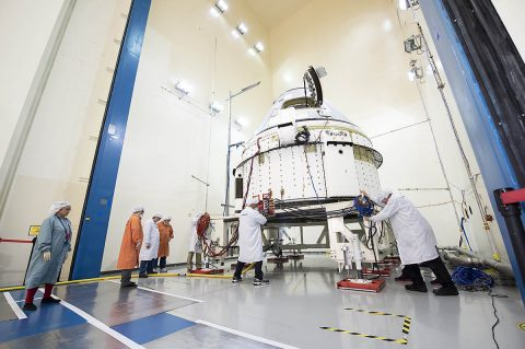 Technicians at the Boeing Space Environment Test Facility in El Segundo, California, position Starliner inside the acoustics test chamber. (Boeing)