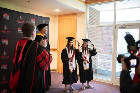 Lidia Yanes Garcia, left, and Claudia Yanes Garcia move their tassels to the left during the ceremony. (APSU)