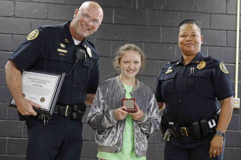 Clarksville Police Department's (L) Captain James Smith and (R) Captain Liane Wilson congratulate (M) Hailie Latham in front of her classmates.
